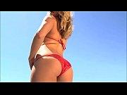 A girl in a red micro bikini is walking in the pool