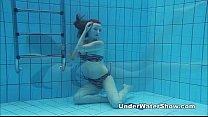 Redheaded cutie swimming nude in the pool