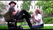 Submissive girl licks man's feet in park