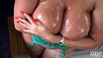 Busty blonde babe Lucy Zara oils her stunning body on the kitchen floor thumbnail