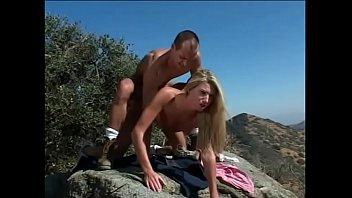 Muscled man gets frisky with adorable blonde girl on a desert landscape