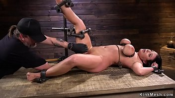 Tied busty brunette in device bondage