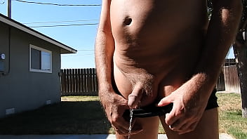 A mature man in his short-shorts whipping out his dick and peeing a stream.
