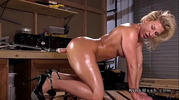 Oiled blonde takes fucking machine anal