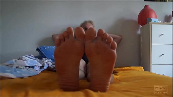 Сын делает усталой маме массаж ног на кровати и